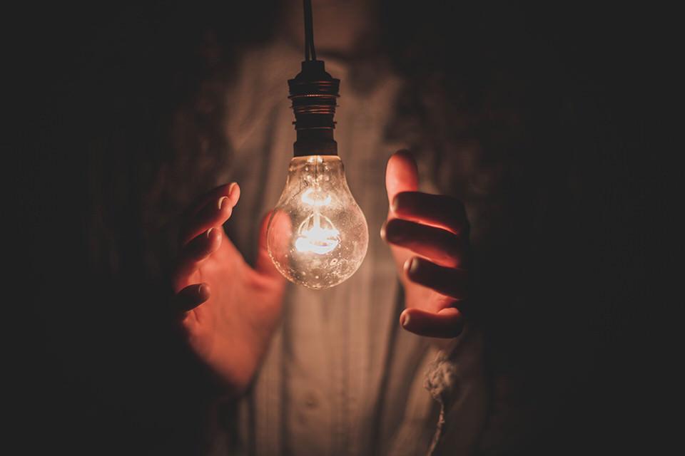 Eine Glühbirne zwischen Händen