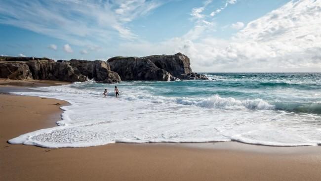 Zwei Menschen springen in den Wellen auf einem Strand, im Hintergrund Felsen.