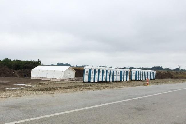 Ein großes weißes Zelt und eine Reihe Toilettenhäuschen an einer Straßen in einer menschenleeren Umgebung.