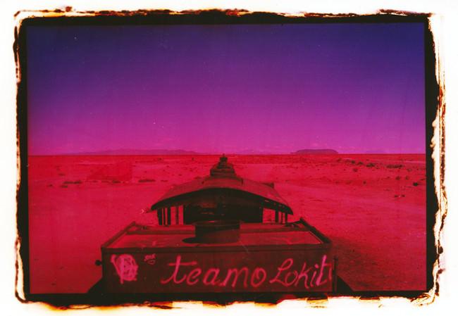 Ein rot-violettes Boot in der Wüste.
