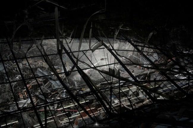 Surreale Landschaft aus zerstörten Gebäuden mit einem Hubschrauber mit Suchscheinwerfer in der Mitte.