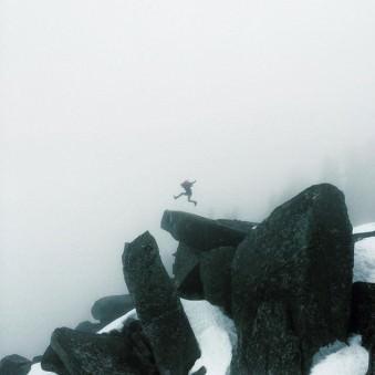 Eine Person springt im Nebel über einige sehr große Felsen.