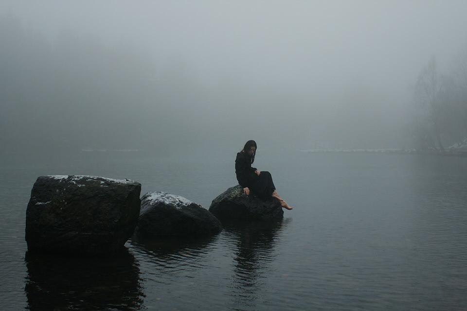 Eine Frau sitzte auf Steinen im Wasser