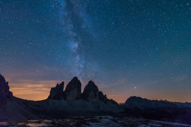 Silhouette eines Gebirges, dahinter der Nachthimmel mit Sternen und Dämmerung.