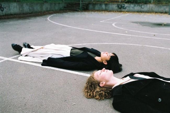 Zwei Menschen liegen auf dem Rücken auf einem betonierten Spielfeld.