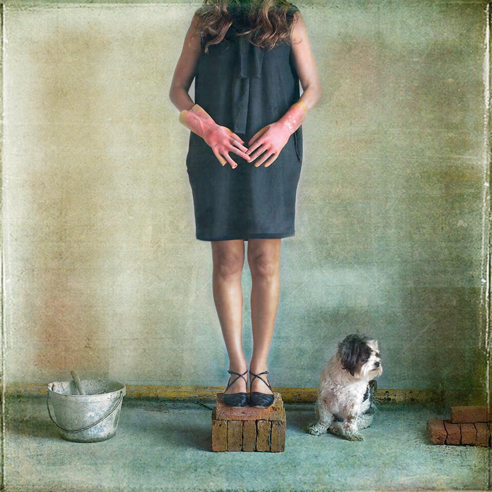 Eine Frau steht auf gestapelten Backsteinen, ein kleiner Hund sitzt daneben.