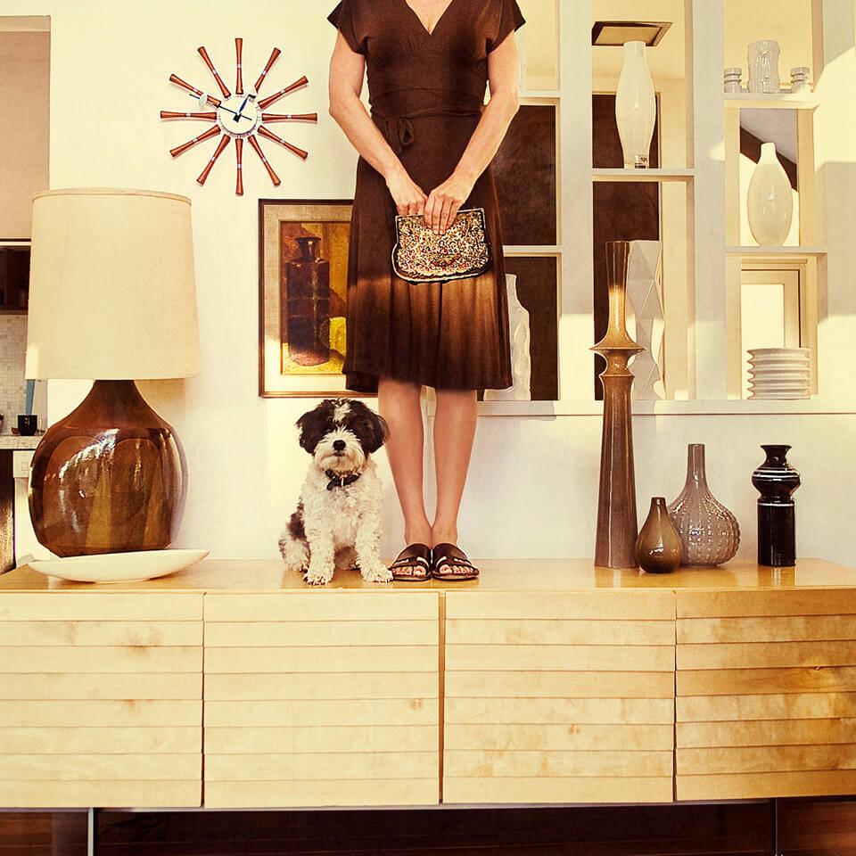Eine Frau und ein Hund stehen auf einem Sideboard.