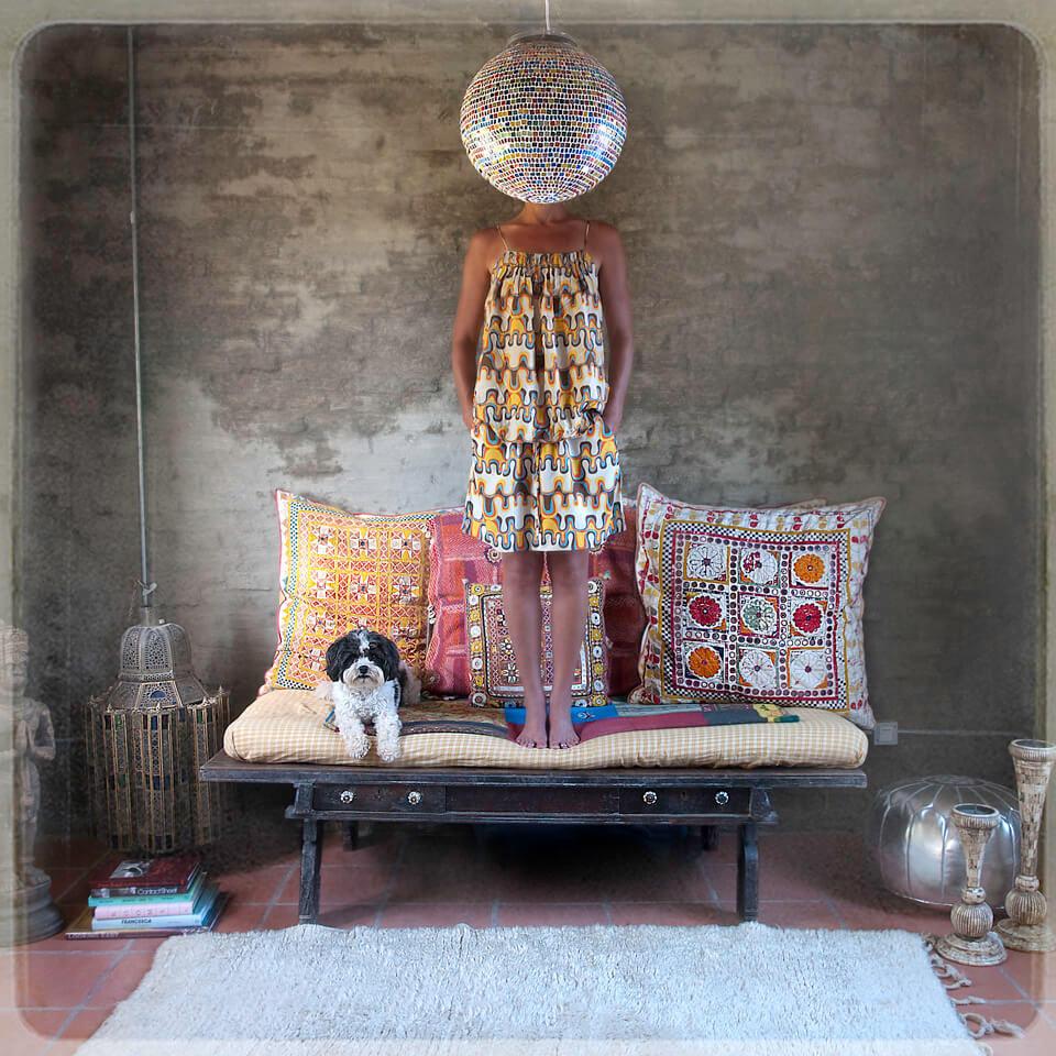 Eine Frau mit einer Discokugel vor dem Gesicht steht auf einem Sofa.