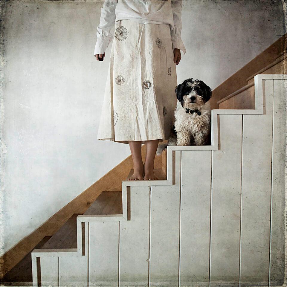 Eine Frau und ein Hund stehen auf einer weißen Treppe.