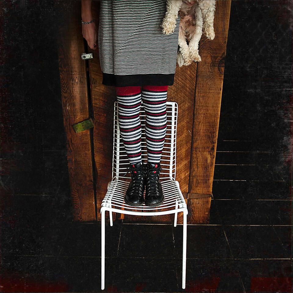 Eine Frau mit gestreifter Strumpfhose steht auf einem Gartenstuhl.