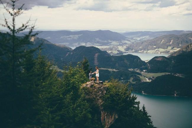 Ein Mann kniet vor einer Frau, sie stehen auf einem Vorsprung in einer weiten Seen- und Gebirgslandschaft.