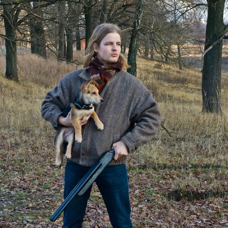 Ein M;ann mit einem kleinen Jagthund auf dem Arm und einem Gewehr in der Hand.