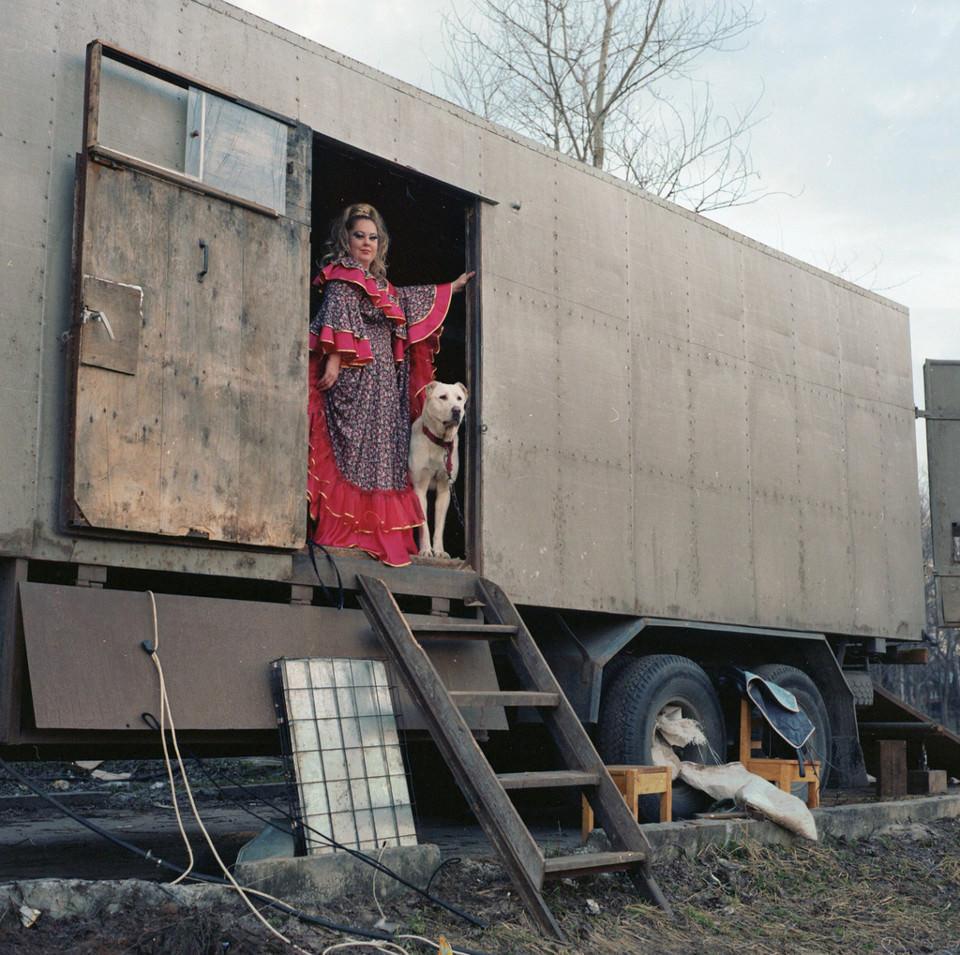 Eine bunt gekleidete Frau neben einem weißen Hund in einem Zirkuswagen.