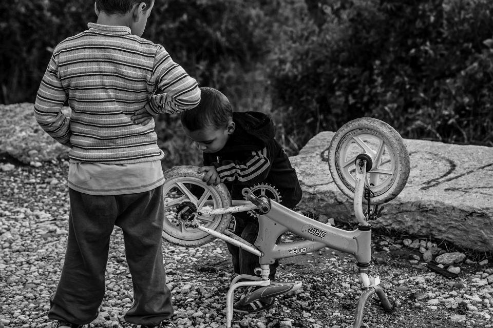 Zwei Jungen reparieren ein Fahrrad.