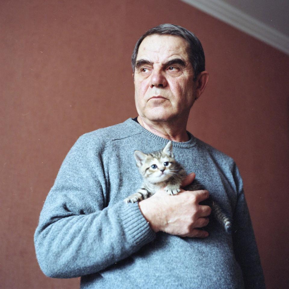 Ein älterer Herr hält ein Kätzchen auf dem Arm.