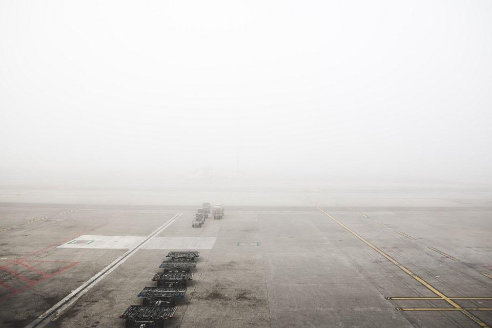Nebelverhangener Parkplatz mit wenigen LKWs.