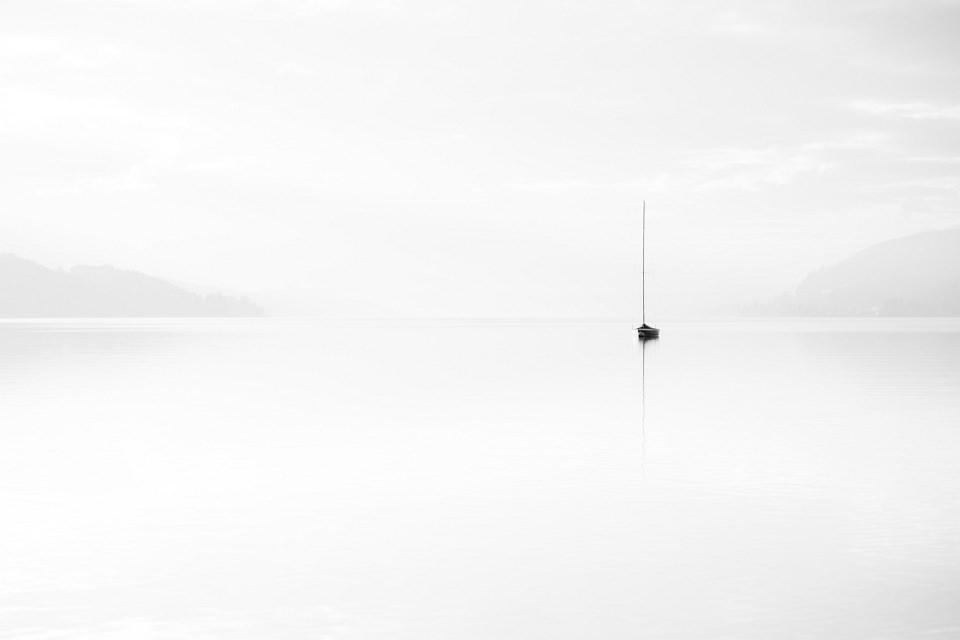 Einzelnes Boot auf weiter, weißer, stiller Seeoberfläche.