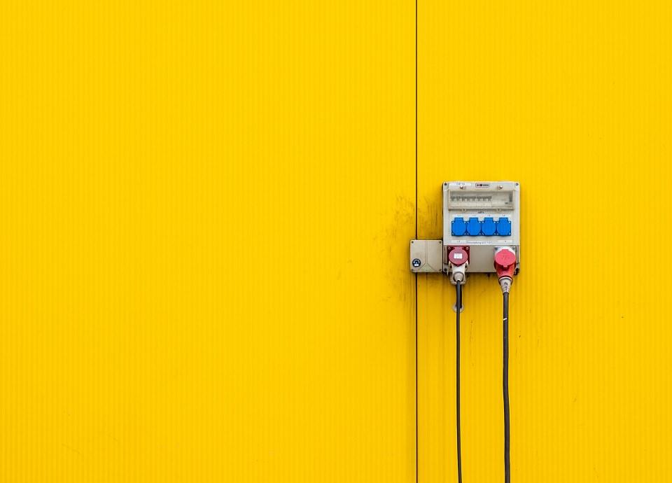 Stecker und Kabel an einer gelben Wand.
