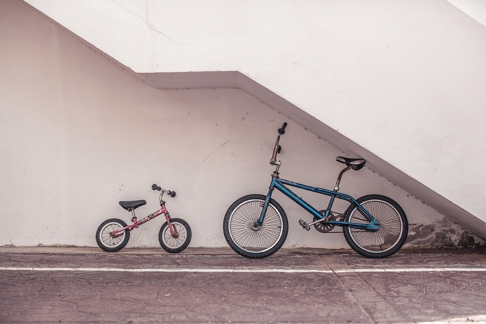 Zwei Fahrräder unter einer Betontreppe.