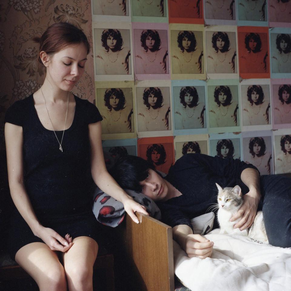 Eine Frau und ein Mann mit einer Katze auf einem Bett.