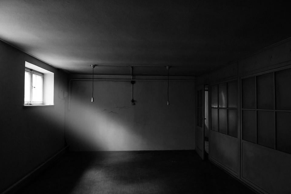 Ein dunkler Raum, in den etwas Licht durch ein kleines Fenster fällt.