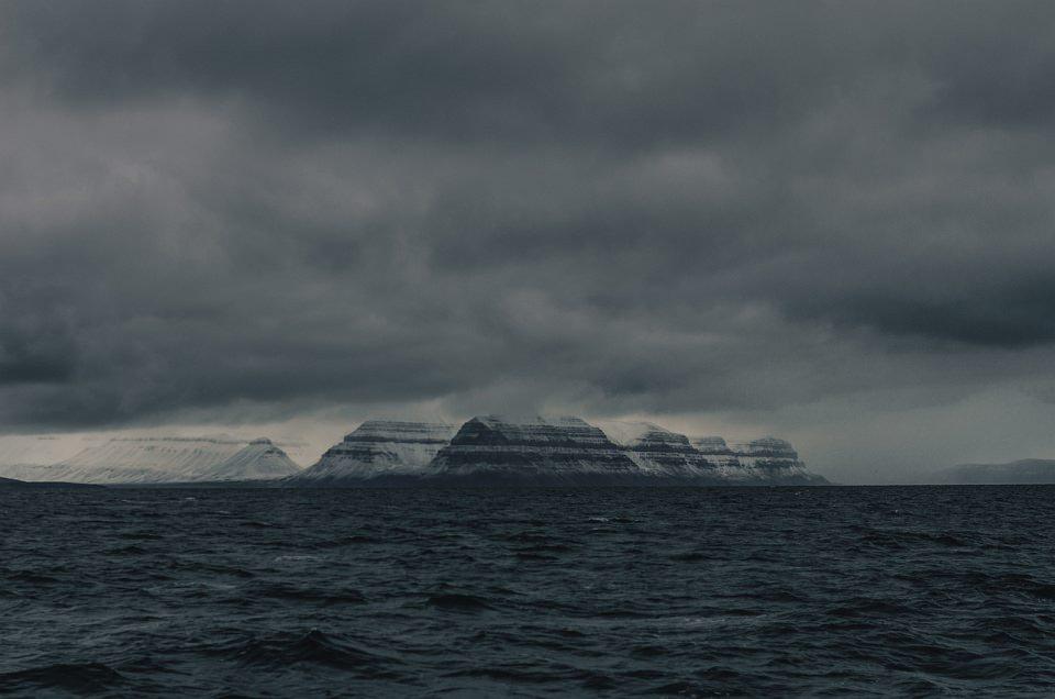 Gletscher zwischen dem offenen Meer und tief hängenden Wolken.