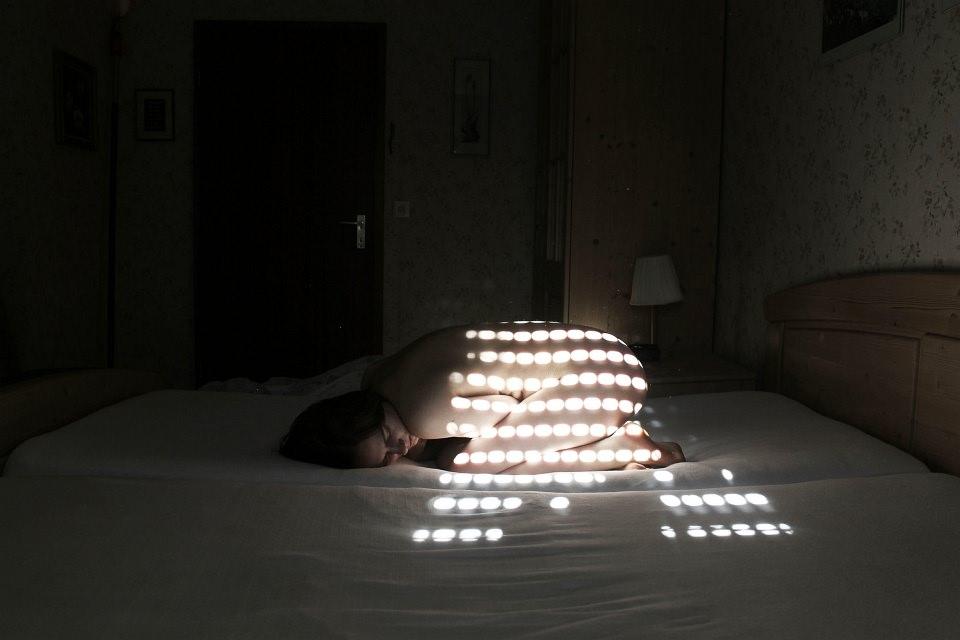 Nackte Frau zusammengekauert auf einem Bett, in einem dunklen Zimmer, auf ihrer Haut Lichtflecken, die durch einen Rollladen fallen.