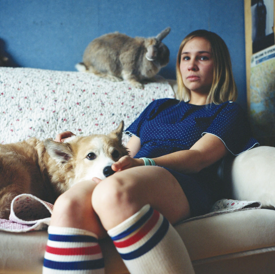 Eine junge Frau sitzt auf nem Sofa, daneben ein Hund und ein Kaninchen.