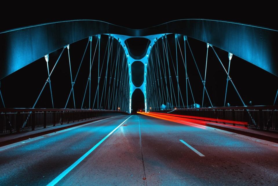 Fahrbahn über eine Brücke, nachts in blauem und rotem Licht.