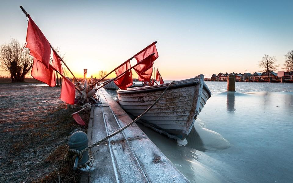 Am Steg festgefrorenes Boot mit roten Fahnen im morgendlichen Gegenlicht.