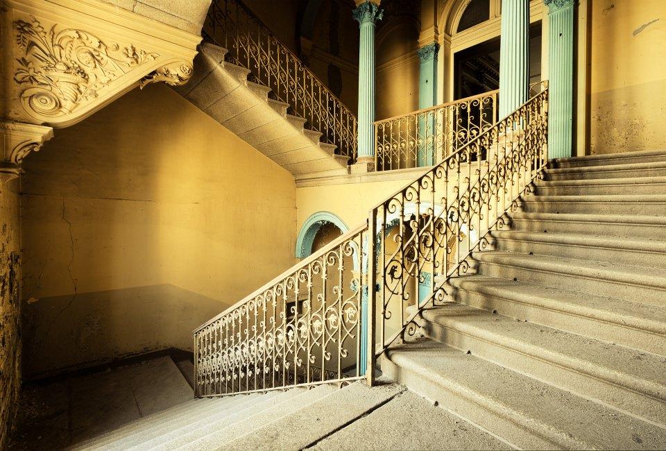 Gelbes Treppenhaus in einem verlassenen Gebäude.
