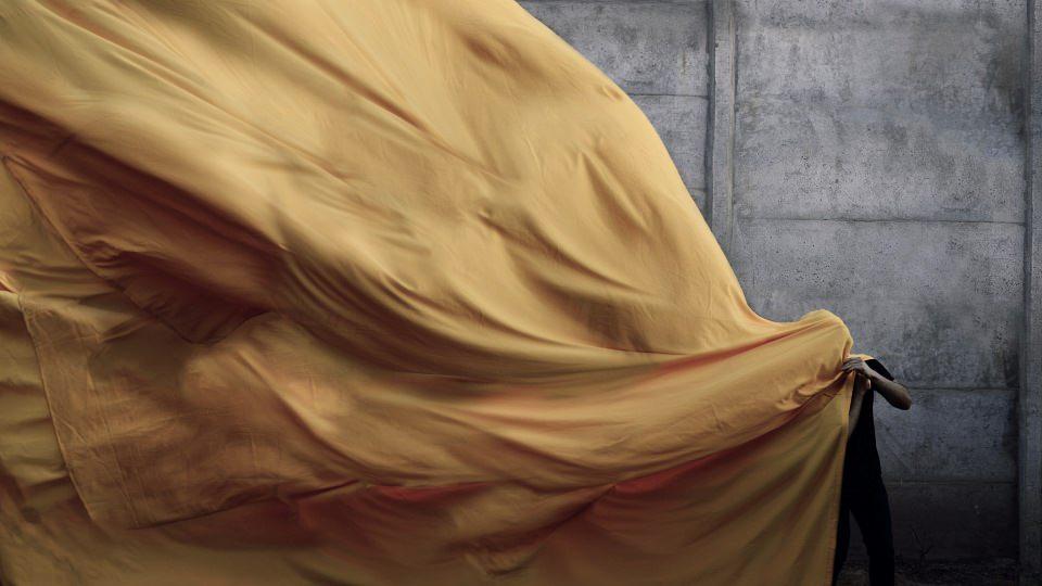 Eine Person steht unter einer sehr großen, wehenden, gelben Stoffbahn.