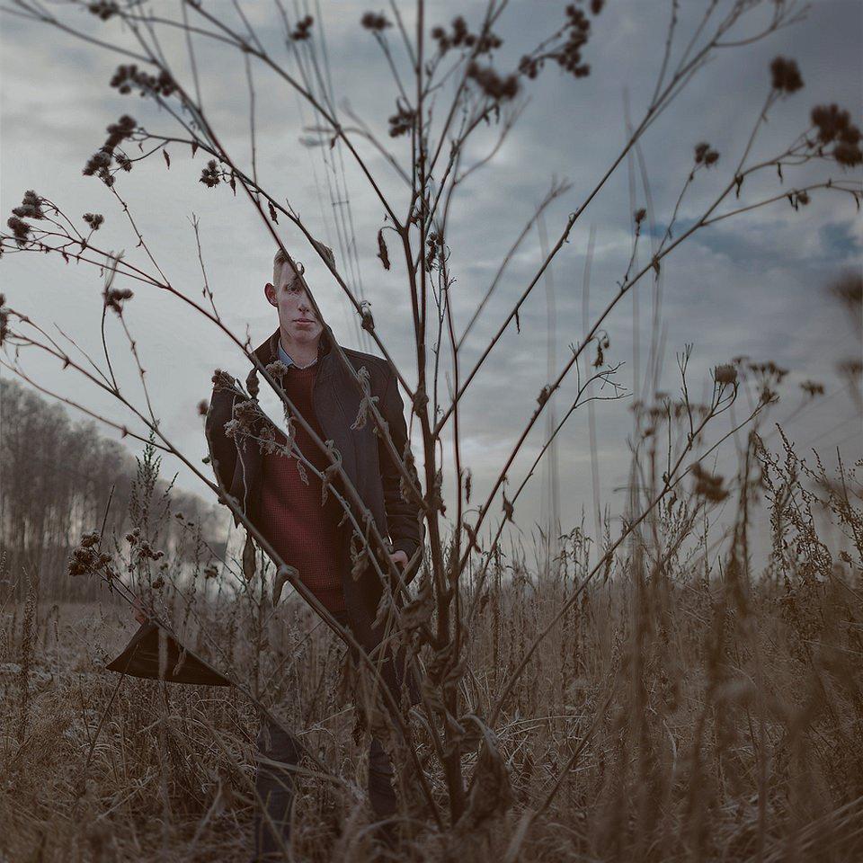 Teile eines Menschen, sichtbar durch Stängel einer vertrockneten Pflanze auf einem wüsten Feld.