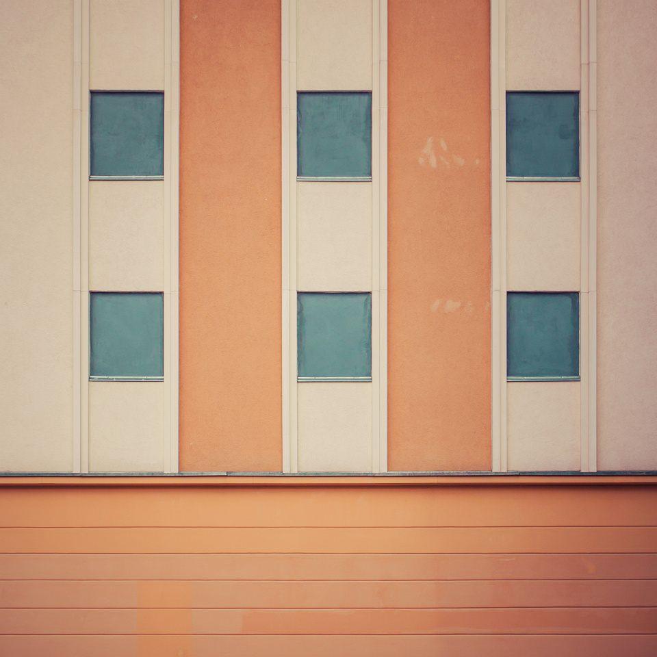 Hauswand in orange mit blauen Fenstern.