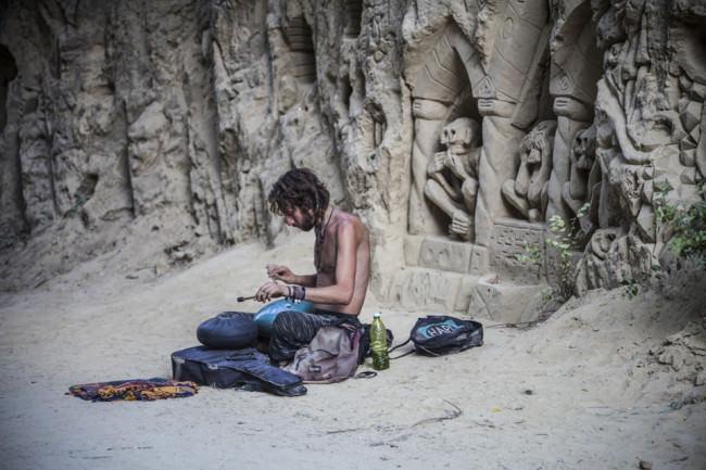 Ein Mann am Strand mit Skulpturen im Hintergrund.