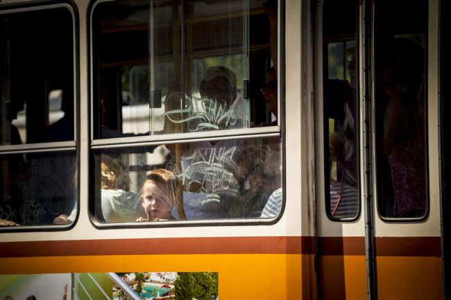 Ein Kind steht im Fenster einer Bahn.