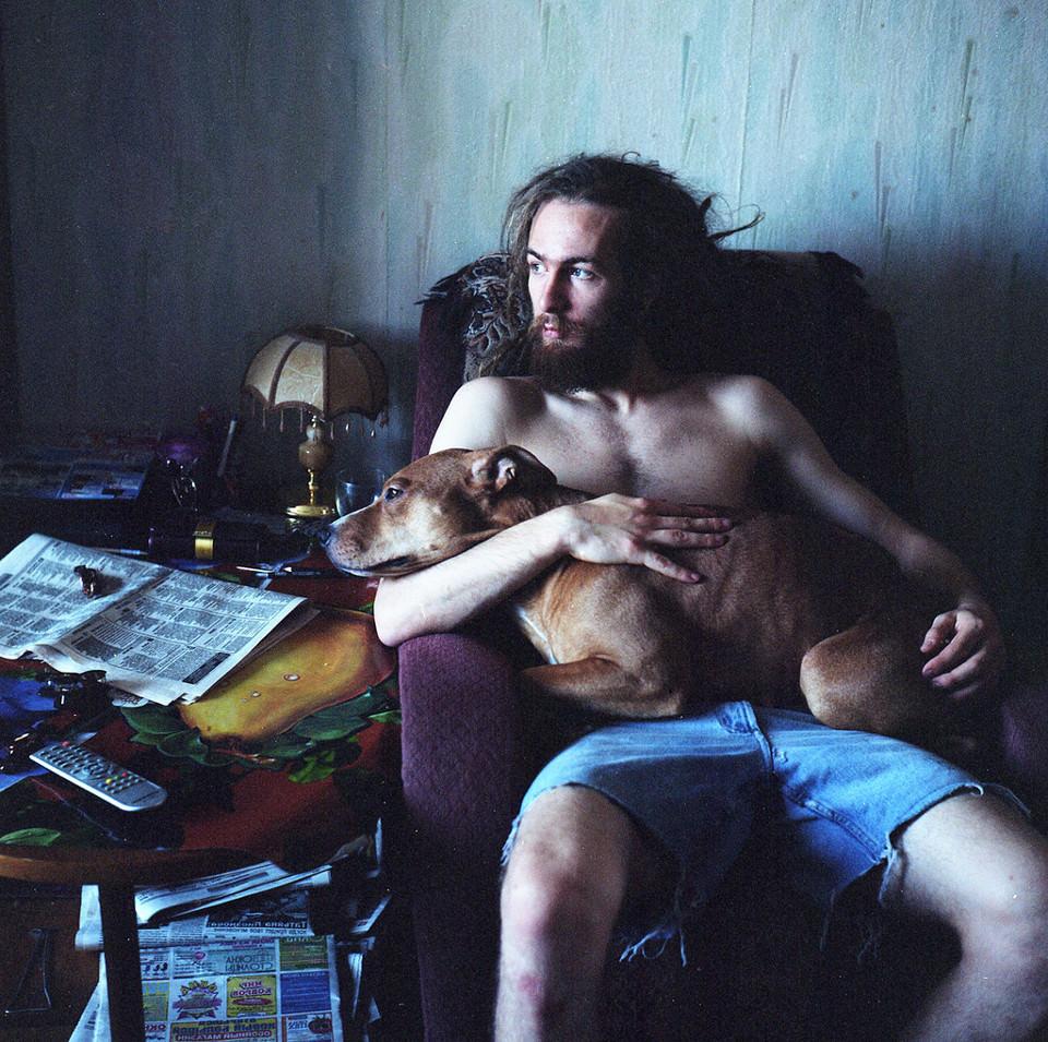 Ein oberkörperfreier Mann sitzt mit einem Hund im Arm auf einem Sessel.
