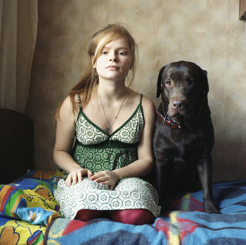 Ein Mädchen und ein Labrador schauen gerade in die Kamera.
