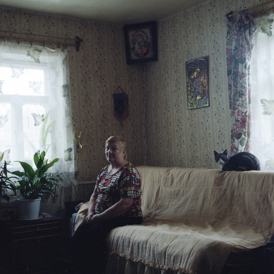 Eine Frau sitzt auf ihrem Sofa, auf der Kopfstütze liegt eine Katze.