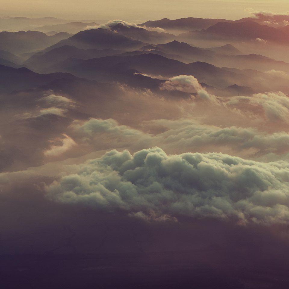 Wolken in verschiedenen Farbschattierungen über einer bergigen Landschaft.