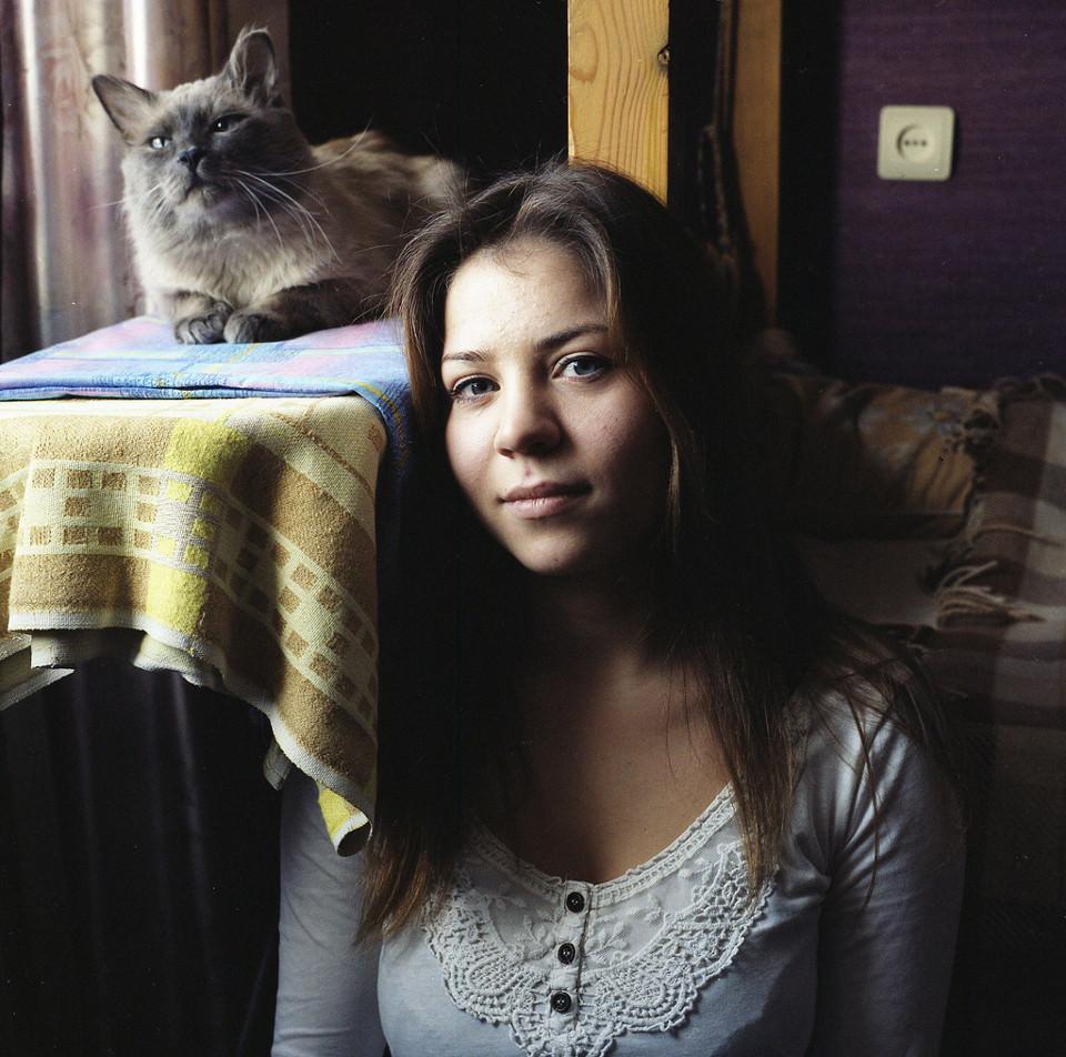 Eine junge Frau lehnt sich an einen Tisch mit einer Katze darauf.