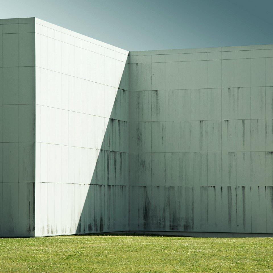 Wand eines hohen weißen Gebäudes vor grüner Wiese.