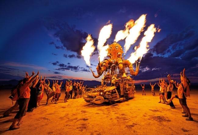 Ein feuerspuckendes Gefährt in Form eines Oktopus, nachts in der Wüste, umgeben von jubelnden Menschen.