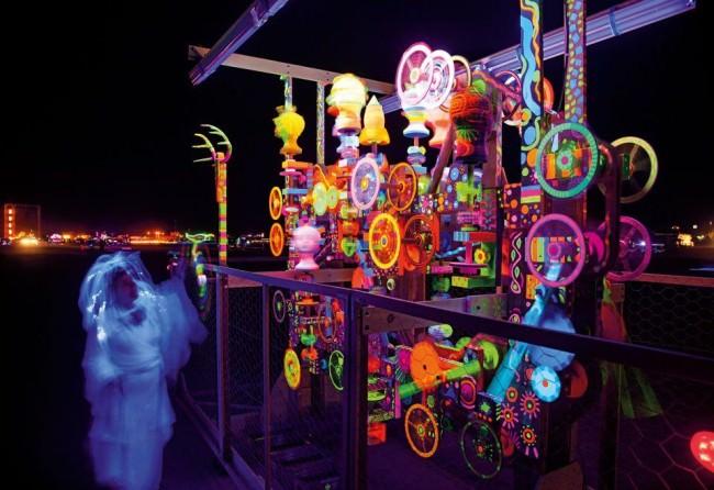 Langzeitbelichtung einer Maschine mit vielen Rädern, bunt leuchtend in der Dunkelheit.