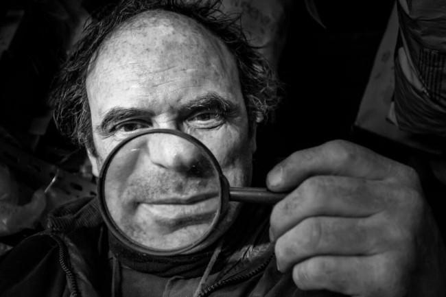 Ein Mann schaut durch eine Lupe