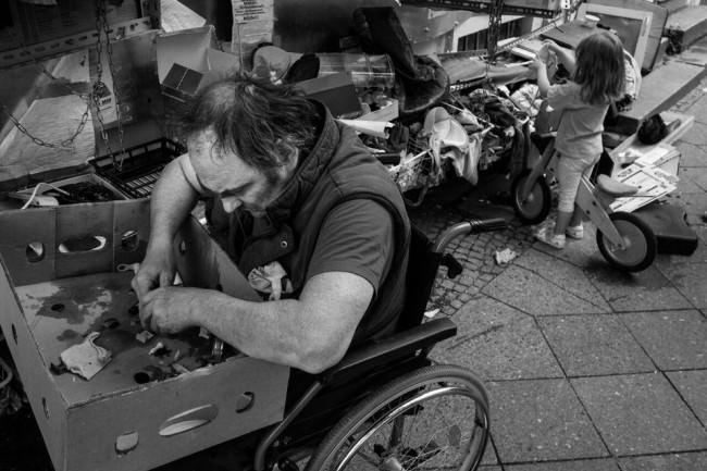 Ein Mann im Rollstuhl und ein Mädchen auf einem Roller wühlen in Kisten