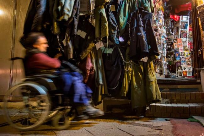 Ein Mann im Rollstuhl fährt an einem Geschäft vorbei