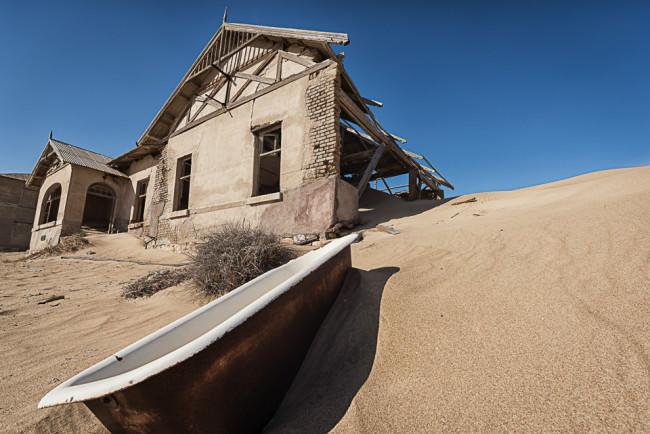 Verfallene Häuser in einer Wüste, davor eine Badewanne.