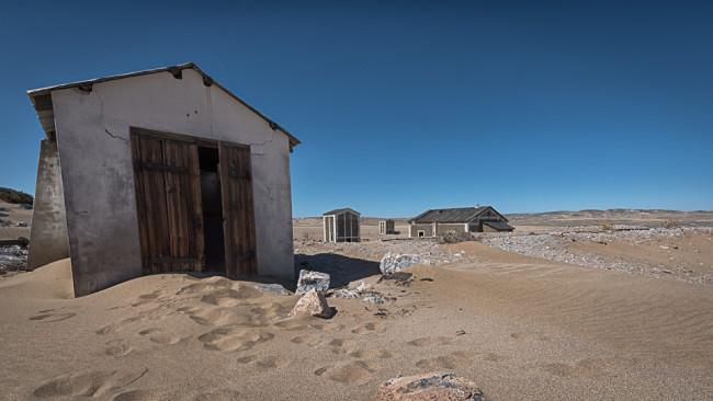 Verfallene Häuser in einer Wüste.