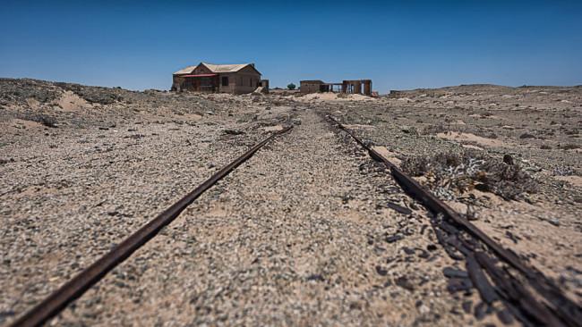 Verfallene Häuser und Bahnschienen in einer Wüste.